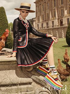Hens at Chatsworth House  are captured in the Gucci Cruise 17 campaign, with a leather jacket and pleated skirt featuring Sylvie stripe trim, and the rainbow platform sneakers.
