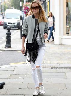 Poppy Delevingne De 10 este outfit de Poppy Delevingne con pantalones pitillo en blanco, sudadera gris, beisbolera en gris y negro, bolso de flecos y zapatillas Converse.