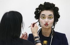 A model has her makeup applied before the Vivienne Westwood Red Label Autumn-Winter 2013 collection presentation during London Fashion Week, February 17, 2013. REUTERS-Suzanne Plunkett
