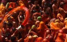 A man flings a pail of orange colored water towards a group of women during Huranga at the Dauji temple in Mathura, India, March 28, 2013