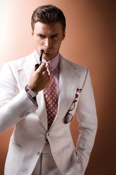 White single-breasted linen twill two-piece suit, pink and white polka-dot cotton shirt, pink and white polka-dot silk tie, gold-plated collar bar and pink and brown print silk pocket square, all Tom Ford; dark brown tortoiseshell acetate sunglasses, Giorgio Armani; Tradition Extra-Thin timepiece in platinum case and brown crocodile strap, Audemars Piguet.