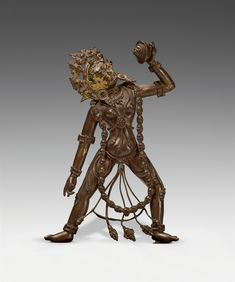 A Tibetan bronze figure of a Sarvabuddha-Dakini. 17th/18th century  A Tibetan bronze figure of Sarvabuddha-Dakini, standing in alidhasana, holding a skull cup in her upraised left hand, wearing a garland of skulls and festooned beaded jewellery and a skull tiara, with her hair falling down her back. Cold gilt to the face. 17th/18th century. Black wooden base.  Height 17 cm