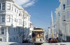 SF Trolly between pretty white victorians down the street with transAmerica in background.....