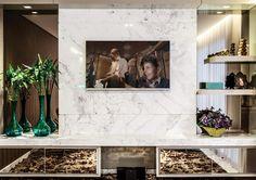Neste projeto da designer Fabiana Visacro, a TV foi disposta em um painel de mármore Piguês, dentro de uma proposta requintada e ousada.