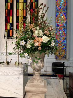 Altar urns filled with white hydrangea, peach roses, peach stock, white delphinium, abelia, and mandavilla