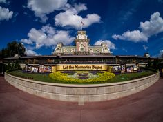 Happy Friday! For today's post, we're taking a very wide look at the Main Street Train Station at the Magic Kingdom. The other day when I was in the park gathering photos for my MiceChat column, the skies weren't great for photography. But, when I was leaving the park, I noticed while walking down Main Street that there were some seriously great Florida clouds that kind of came out of nowhere. Having my fisheye lens with me, I thought it could make for a great scene since the Mickey floral…