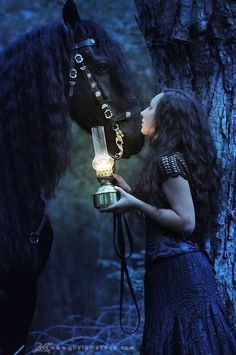 Strong black horse and lady with a lantern on a moonlit walk.