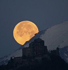 The full moon sets behind the Alps and the Sacra di San Michele on Mount Pirchiriano in northern Italy  Photograph: Stefano De Rosa/Royal Observatory
