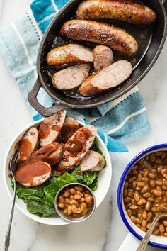 Bratwurst sausages with southern style collard greens, baked beans and a smoky…
