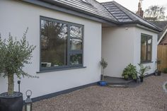 The cool anthracite grey windows stand out beautifully against the white render. Modern Bungalow Exterior, White Exterior Houses, Modern Bungalow House, Grey Exterior, Bungalow Homes, Modern Farmhouse Exterior, House Paint Exterior, House With Grey Windows, House Windows