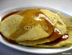 A stack of pancakes slathered with butter and syrup.