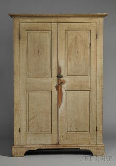 New England Grain Painted Pine Cupboard, 19th century, the two paneled doors opento an interior of eight shelves, all on bracket feet, early surface of blue paint with sepia grain painting, 85.5 h. x 54 W. x 21.5 D.