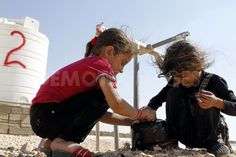 Syrian refugee girls cleans a tea kettle with a water tap in al-Zaatari refugee camp, near the Syrian border north of Amman.