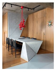 An ultra modern touch, triangular-end concrete table in this tri-level triplex. Architect Guto Requena.