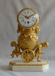 Antique French ormolu clock of two cupids pulling a cart carrying an urn full of grapes. - Gavin Douglas Antiques