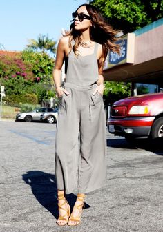 Ashley Madekwe wears a olive green overall with a black bandeau, suede brown sandals, sunglasses and a silver necklace.