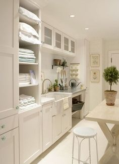 white painted cabinets with green glass pulls, some open storage, laundry sink with nickel hardware, folding area, framed botanicals, white painted vintage metal stool, topiary, orchid, potting area as well, lots of space & light - timeless