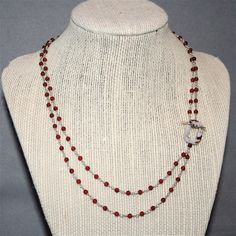 3mm round carnelian beads are rosary linked together making a double strand necklace with sterling silver wire. A toggle closure with a light