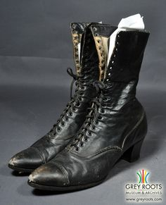 A pair of factory-made, ladies', high, lace-up boots, of the Empress Shoe brand. These boots were made in Canada and are black leather with a white cotton lining. They have pointed toes, with a perforated leather piece stitched across the toe. Grey Roots Museum & Archives Collection.