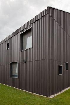 Die Fassade und das Satteldach sind mit Faserzement-Wellplatten verkleidet