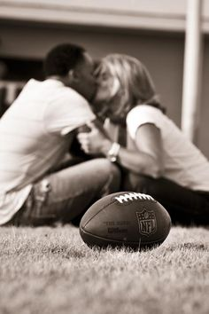 couple sitting on ground kissing with football in front of them