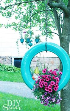 How to make a DIY painted tire swing flower planter. This rustic planter idea is a cute way to recycle old used tires to make a hanging flower planter or plant holder. It's a great way to dress up porches or your outdoor spaces at your home. #DIYgardening #tireswing
