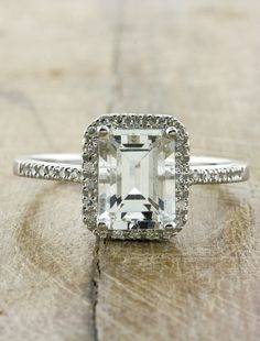 This Vintage Inspired Engagement Ring features an Emerald Cut Aquamarine surrounded by a Halo of Diamond Accents in a Classic Cathedral Setting