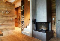 Un moderno caminetto in calcestruzzo riscalda il living della villa in montagna in Austria. Su misura, i vani porta legna diventano motivo di arredo. Trofei animali e un paio di sci vintage vivacizzano la parete