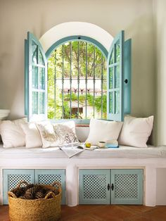 Love this little seat, white and touches of blue with an arch window.