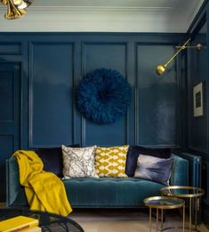 Wooden paneling, velvet and this navy, yellow and brass colour scheme make this living room really luxurious! I love the juju hat on the wall also.