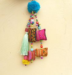 I make these beautiful tassel purse charms and use hmong vintage fabric to make the small parcels, then I add beautiful colored bead work If you would