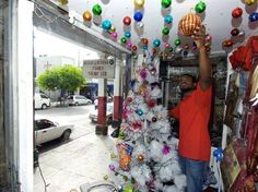 Ajani Barrett, an employee at Matar and Hanna Family Store on King Street, downtown Kingston, yesterday decorates the showcase for Christmas two days ahead of this year's Christmas in the City, Downtown Comes Alive. - Norman Grindley/Chief Photographer