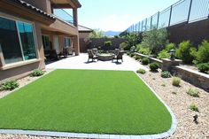 A simple artficial turf project. This was such a joy to do as it created a large usable space for our clients. The retaining wall in back helped to break up the one dimension of the planter bed. The use of the coach lights along the wall help to illuminate the back at night. This is definitly one of our favorites.