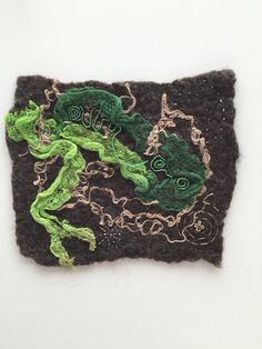 Nuno felt with felt technique, integration of hemp fibers and glass beads embroidery and metallic thread.