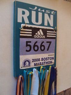 running medals hanger with running racing bibs by runningonthewall
