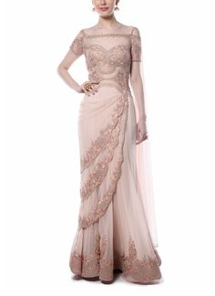 This gorgeous drape saree in light pink by Mandira Wirk exudes a very graceful and feminine vibe with all its pretty detailing. It features a stunning off-shoulder bodice adorned with ethnic zari and resham embroidery, sheer and cut-out detailing. It has been complemented beautifully with an embellished scalloped tiered drape design