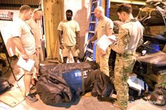 Pararescuemen of the 82nd Expeditionary Rescue Squadron at Camp Lemonnier, Djibouti, discuss the best way to prepare equipment for a mission, Thursday, April 3, 2014. (MICHAEL ABRAMS/STARS AND STRIPES)