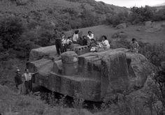 Esta fotografía muestra a un grupo de gente encima del monolito de Tláloc en la localidad de San Miguel Coatlinchan,Estado de México. En 1964, fue extraído para ser colocado en su ubicación actual a las afueras del Museo de Antropología. El recorrido requirió la construcción de un armazón de vigas de acero para alzar el monolito y un remolque especial de más de 20 ejes jalado por dos tractocamiones.