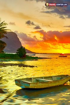 A landscape view of a fishing boat amidst the sunset backdrop in Le Morn Brabant, Mauritius features the picturesque skyline and lagoon.  #mauritius #sunset #boats #itsallabouttravel #travelcenteruk