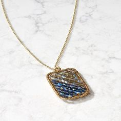 """Facetted, iridescent beads are framed in delicate brass on this swinging pendant necklace handcrafted by makers in India. Artisan partner, Tara Projects, works to change the lives of India's """"untouchables"""" by eliminating unfair trade practices and child labour. This necklace's length can be extended for more flexibility."""