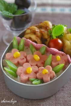 Simple, but still pretty, an excellent choice for a quick and easy bento. Ham flowers with a corn kernel center, and cut green beans for leaves.