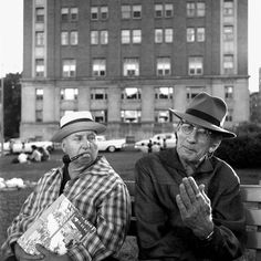 Two men with hats sitting on a bench, one with a pipe and the other with glasses. Untitled, Undated