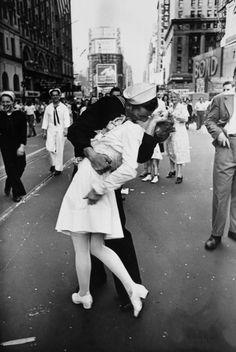 """V-J Day in Times Square (1945) - Essa imagem, registrada pelo fotógrafo Alfred Eisenstaedt registra a euforia americana com o fim da II Guerra Mundial. Segundo o fotógrafo, esse jovem marinheiro estava beijando todas as mulheres que encontrava pela praça, fosse ela """"uma avó, magricela, gordinha…""""."""
