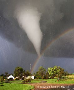 The scene might have been considered serene if it weren't for the tornado. During 2004 in Kansas, storm chaser Eric Nguyen photographed this budding twister in a different light -- the light of a rainbow. Pictured above, a white tornado cloud descends from a dark storm cloud. The Sun, peeking through a clear patch of sky to the left, illuminates some buildings in the foreground. Sunlight reflects off raindrops to form a rainbow. By coincidence, the tornado appears to end right over the rainbow.