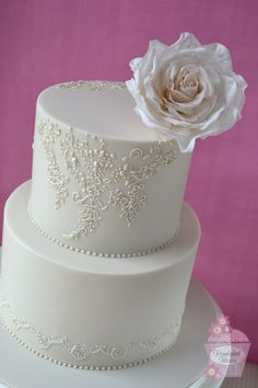 """Ivory wedding cake with hand piped decoration inspired by the bride's Blue by Enzoani """"Iva"""" wedding dress, topped with a sugar rose."""