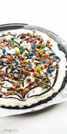 This Frozen Ice Cream Dessert Pizza is THE no bake summer dessert you need! A Dairy Queen Copycat Treatzza Pizza, it has an Oreo fudge crust topped with ice cream, fudge sauce and M&M's! http://www.thereciperebel.com/frozen-ice-cream-dessert-pizza-treatzza-pizza/