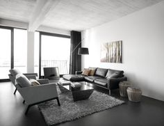 black and white modern living room set consisting of black leather sofa two white chairs modern black glass coffee table fluffy grey area rug black laminated floors modern floor lamp of Be Simple yet Modern with These Black and White Living Room Sets