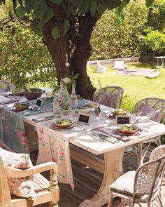 Mesas y sillas de madera pintada de blanco y caminos de mesa de varios estampados