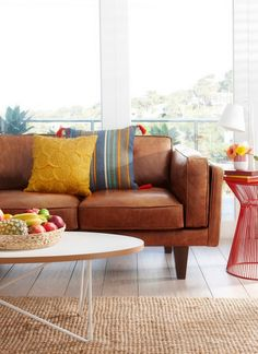 Seriously Contemplating a Leather Couch - love that blue/yellow/grey pillow.