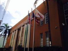 Cámara de comercio  9:02  a.m  como podemos observar en esta institución  izaron las tres banderas por consiguiente el protocolo ha sido incorrecto ya que en días fin de semanas no se deben colocar las banderas,  también podemos observar como colocaron la bandera de Puerto Rico del color azul incorrecto . De igual forma podemos ver como siguen el protocolo colocando la bandera de Estados Unidos al extremo derecho de la bandera de Puerto Rico.